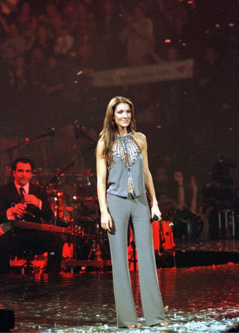 <p>For a concert in Montreal, Canada, Celine wore a flattering grey-blue matching set. The trousers are all business, whereas the belly-baring top is adorned with gems and beads to relax the look.</p>
