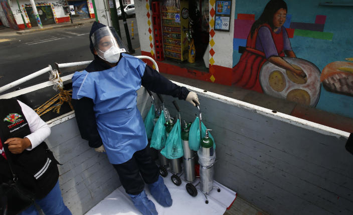 City worker Alexis Hernandez rides in the back of a cargo truck transporting tanks of oxygen for COVID-19 patients, in the Iztapalapa borough of Mexico City, Friday, Jan. 15, 2021. The city offers free oxygen refills for COVID-19 patients. (AP Photo/Marco Ugarte)