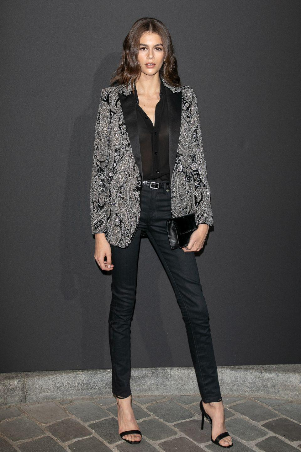 <p>The star teamed a silver and black blazer with a pair of black cigarette trousers and black clutch for a party in Paris, July 2018</p>