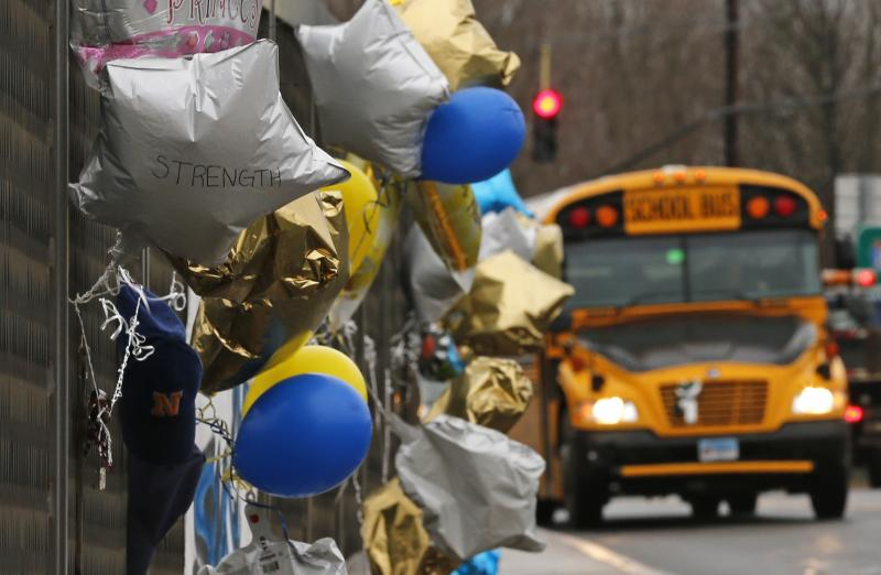 A school bus rolls towards a memorial for victims of the school shooting in Newtown, Conn., Tuesday, Dec. 18, 2012. Classes resume Tuesday for Newtown schools except those at Sandy Hook. Buses ferrying students to schools were festooned with large green and white ribbons on the front grills, the colors of Sandy Hook. At Newtown High School, students in sweatshirts and jackets, many wearing headphones, betrayed mixed emotions.  Adam Lanza walked into Sandy Hook Elementary School in Newtown,  Friday and opened fire, killing 26 people, including 20 children, before killing himself. (AP Photo/Charles Krupa)