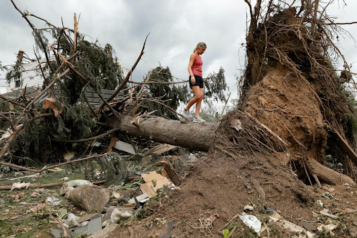 A youngster walks on the trunk of a fallen tree Wednesday, May 29, 2019, in Dayton, Ohio, as cleaning efforts begin in a neighborhood damaged by a tornado storm system that passed through the area on Monday. Tens of thousands of Ohio residents were still without power or water in the aftermath of strong tornadoes that spun through the Midwest.