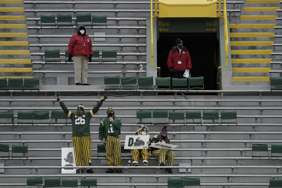 Fans take their socially distanced seats in Lambeau Field before an NFL divisional playoff football game between the Los Angeles Rams and Green Bay Packers, Saturday, Jan. 16, 2021, in Green Bay, Wis. (AP Photo/Morry Gash)
