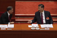 Chinese President Xi Jinping, right, chats with Wang Yang, chairman of the Chinese People's Political Consultative Conference (CPPCC) during the opening session of China's National People's Congress (NPC) at the Great Hall of the People in Beijing, Friday, March 5, 2021. Premier Li Keqiang has set a healthy economic growth target and vowed to make this nation self-reliant in technology amid tension with Washington and Europe over trade and human rights. (AP Photo/Andy Wong)