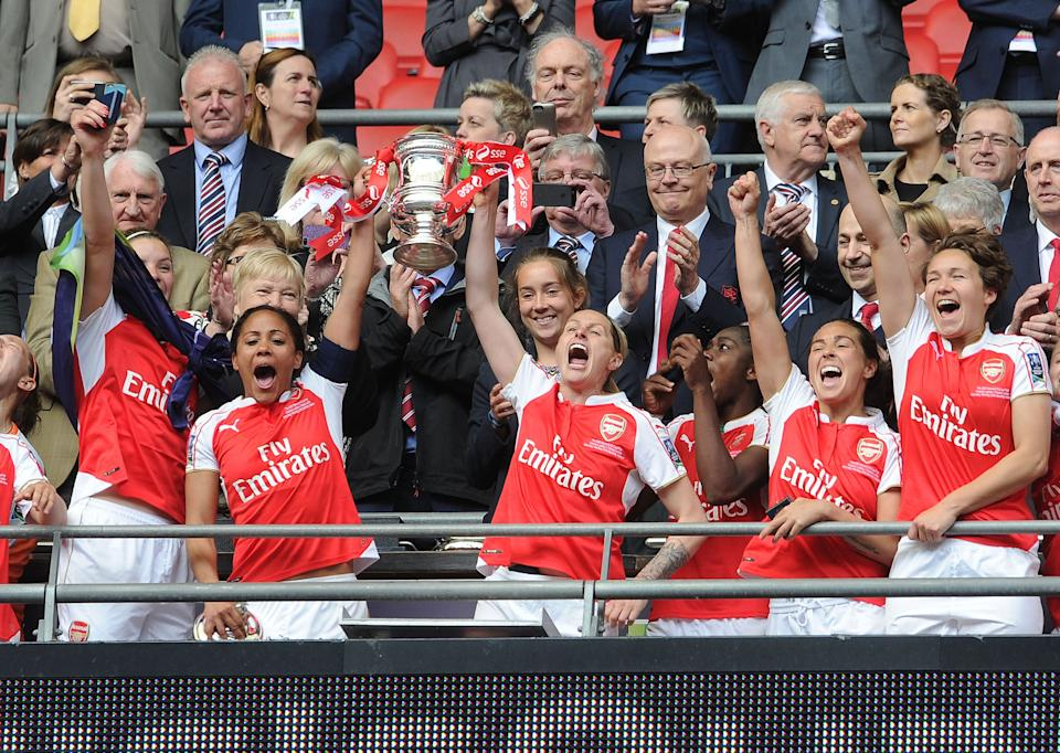 Smith lifts the FA Cup trophy with Alex Scott in 2016Arsenal FC via Getty Images