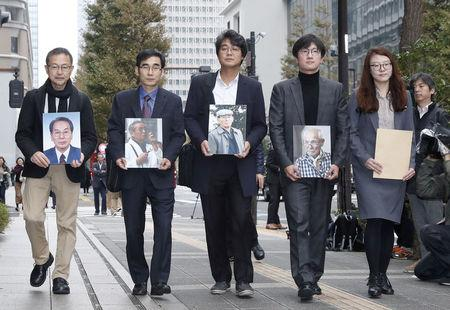 Lawyers and activists hold photos of South Korean plaintiffs who were forced to work for a Japanese firm during World War Two as they visit Nippon Steel & Sumitomo Metal Corp's headquarters building in Tokyo