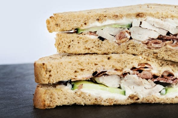 Detail of a sliced chicken and bacon salad sandwich on slate background