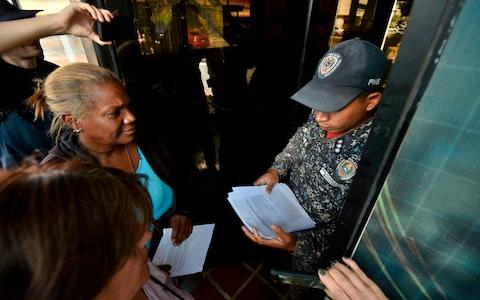 Supporters of Mr Guaido took amnesty letters to military posts on Sunday in a bid to persuade soldiers to come over to his side - Credit: Luis Robayo/AFP