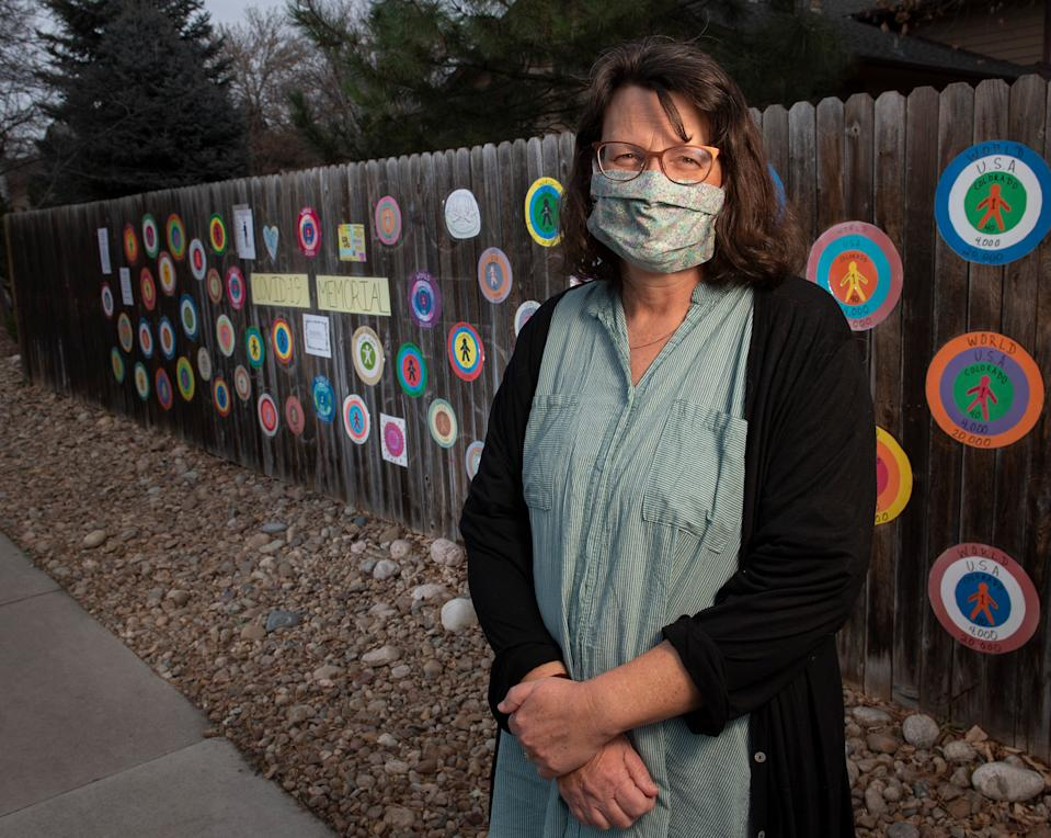 Sara Steen stands in front of the COVID-19 memorial honoring the Larimer County residents who have died from the virus as of early October in Fort Collins, Colo. After the emblems on the memorial were vandalized, a neighborhood-wide effort restored the memorial in less than two weeks.