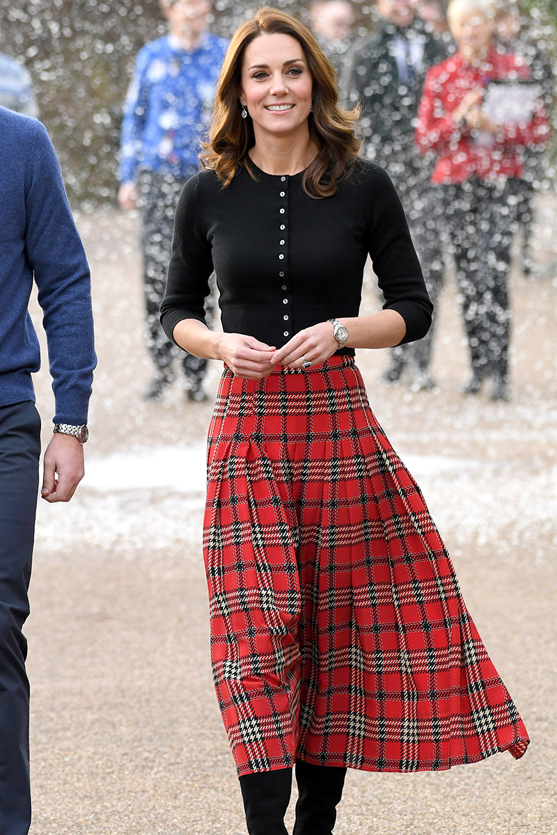 <p>Kate rocked her own red tartan 'fit consisting of a pleated midi skirt and button up cardigan at Kensington Palace in December 2018.</p>