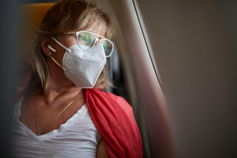 Middle-age Traveler in KN95 Mask Looking Out Airplane Window