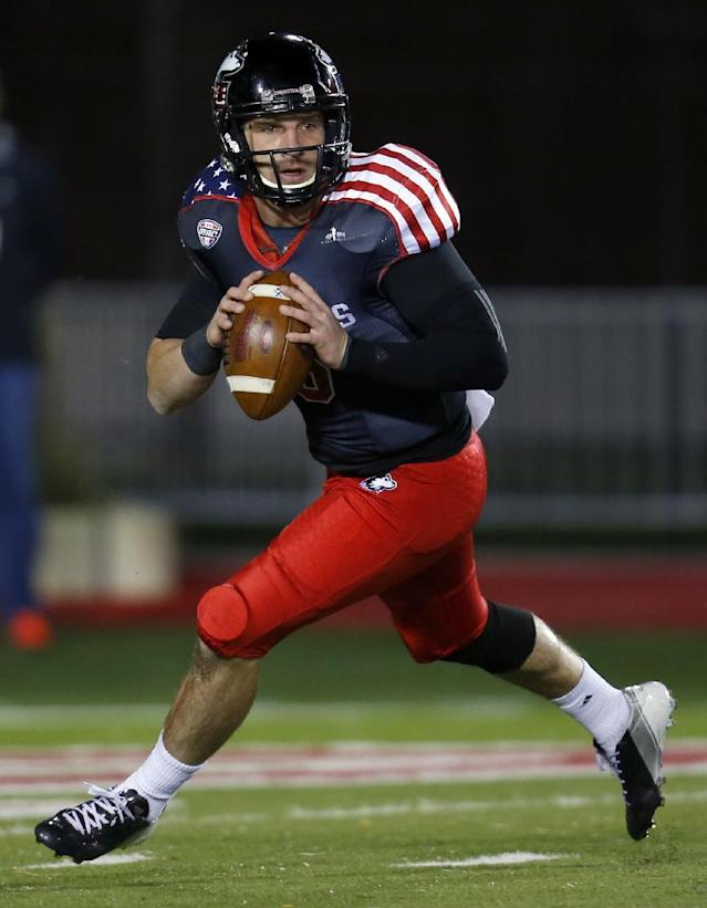 In this Nov. 13, 2013, photo, Northern Illinois quarterback Jordan Lynch looks to make a pass during the first half of an NCAA college football game against Ball State in DeKalb, Ill. Lynch will make a run at history Thursday night, Dec. 26, when he suits up for the final time for No. 24 Northern Illinois in the Poinsettia Bowl against Utah State. Lynch already owns the major college record for yards rushing for a quarterback with 1,881. With 119 yards, he can become the first player to rush for 2,000 yards and throw for 2,000. (AP Photo/Jeff Haynes)