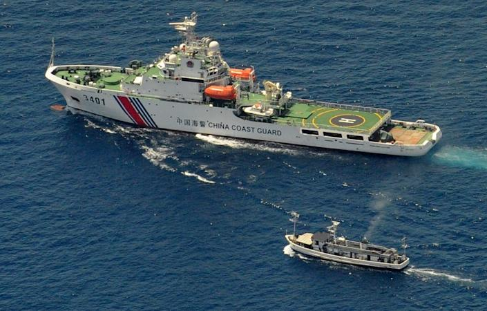 A China Coast Guard ship (top) and a Philippine supply boat were engaged in 2014 stand off in the South China Sea (AFP Photo/Jay Directo)