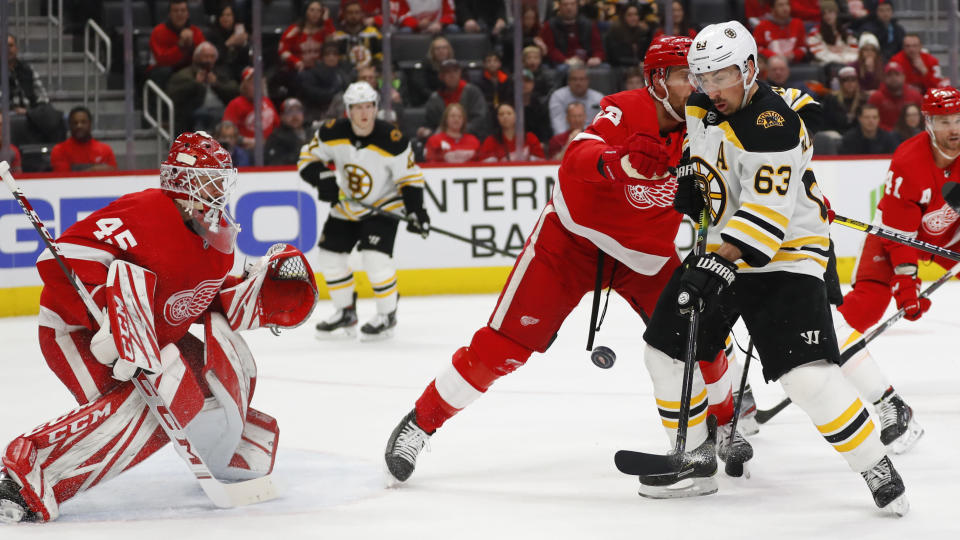 Boston Bruins left wing Brad Marchand (63) tries to redirect a shot as Detroit Red Wings goaltender Jonathan Bernier (45) defends in the first period of an NHL hockey game Sunday, Feb. 9, 2020, in Detroit. (AP Photo/Paul Sancya)