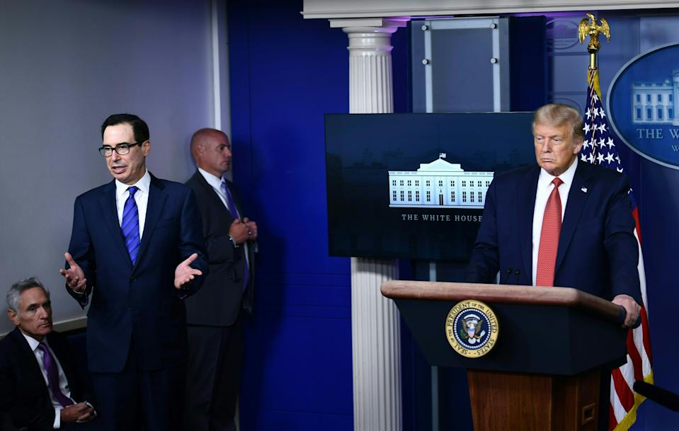 US President Donald Trump listens to Treasury Secretary Steven Mnuchin in the Brady Briefing Room of the White House in Washington, DC, on August 10, 2020. (Photo by BRENDAN SMIALOWSKI/AFP via Getty Images)