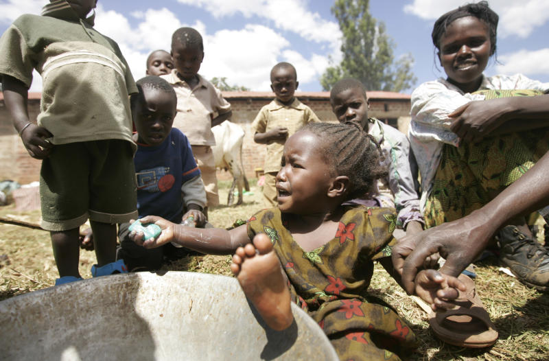 FILE - In this Sunday, Jan. 6, 2008 file photo, a young displaced girl washes herself with soap from a metal bowl in a makeshift camp in Noigam Primary School in Kachibora village, Kenya, following post-election violence. A treaty that African nations hope will lead to the fair and humane treatment of people displaced in their own countries went into force Thursday, Dec. 6, 2012, more than three years after it was conceived by the African Union. (AP Photo/Ben Curtis, File)