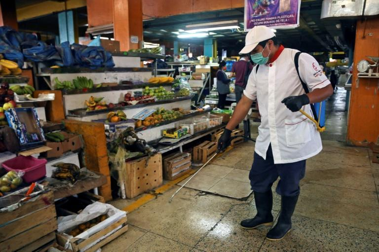 An employee wears a face mask and gloves while disinfecting the Santa Clara market in Quito, Ecuador
