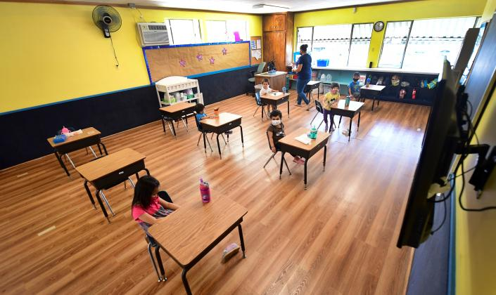 Children in a pre-school class wear masks and sit at desks spaced in Monterey Park, California on July 9, 2020. (Photo by FREDERIC J. BROWN/AFP via Getty Images)