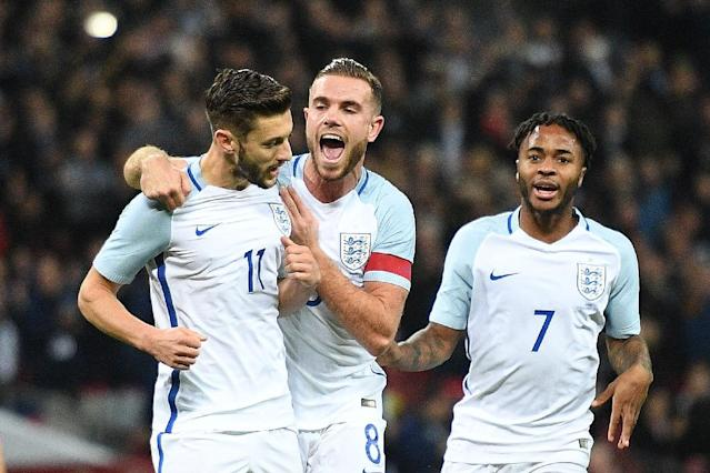 England's midfielder Adam Lallana (L) celebrates scoring his team's first goal from the penalty spot with England's midfielder Jordan Henderson (C) and England's midfielder Raheem Sterling during the friendly match against Spain November 15, 2016 (AFP Photo/Justin Tallis)