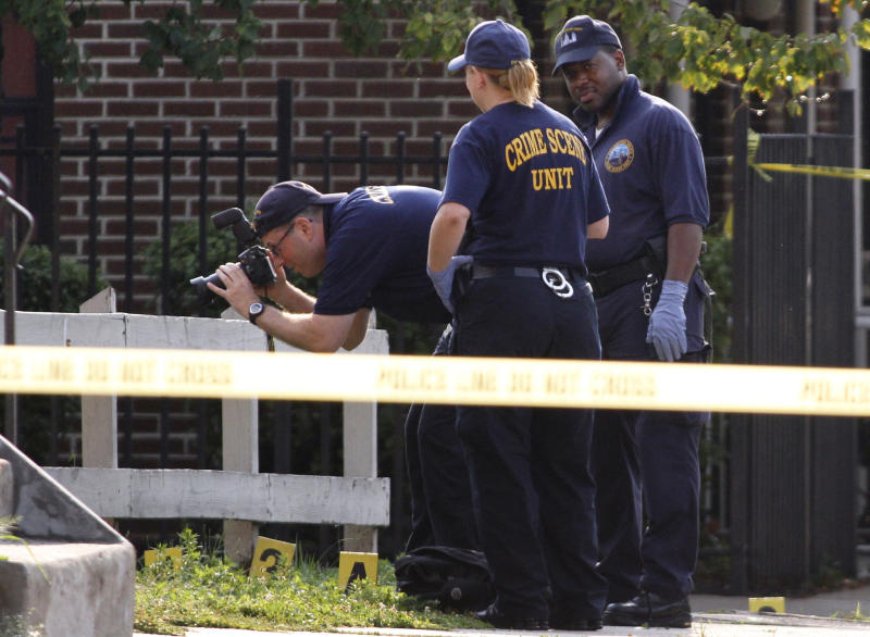 Police investigate the crime scene after an off-duty Philadelphia police officer was shot and killed, Saturday, Aug. 18, 2012, in North Philadelphia. Police said the officer had just gotten off his overnight shift and was not wearing his uniform as he walked along Cecil B. Moore Avenue, where he was shot multiple times just before 6 a.m., Saturday. The officer later died at the hospital. (AP Photo/Joseph Kaczmarek)