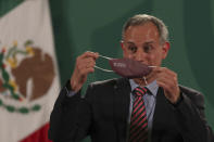 Mexico's assistant health secretary Hugo Lopez-Gatell removes his protective face mask during his last daily press conference to address COVID-19, at the National Palace in Mexico City, Friday, June 11, 2021. (AP Photo/Marco Ugarte)