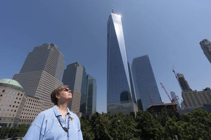 Désirée Bouchat poses for a photo at the World Trade Center, Friday, Aug. 6, 2021, in New York. At first, people figured the plane crash at the north tower was accidental. There was no immediate evacuation order for the south tower. But James Patrick Berger ushered Bouchat and other Aon Corp. colleagues to the elevators, then turned back to check for more people. (AP Photo/Mark Lennihan)