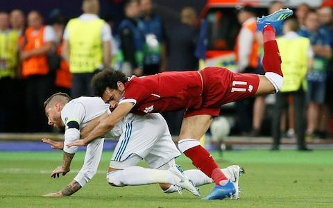 <span>Mohamed Salah falls awkwardly under a challenge from Sergio Ramos </span> <span>Credit: Reuters </span>