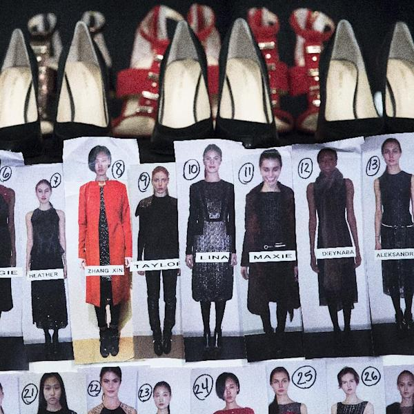Shoes rest on a table beside a look board backstage before the Carmen Marc Valvo Fall 2014 collection is modeled during Fashion Week, Friday, Feb. 7, 2014, in New York. (AP Photo/John Minchillo)