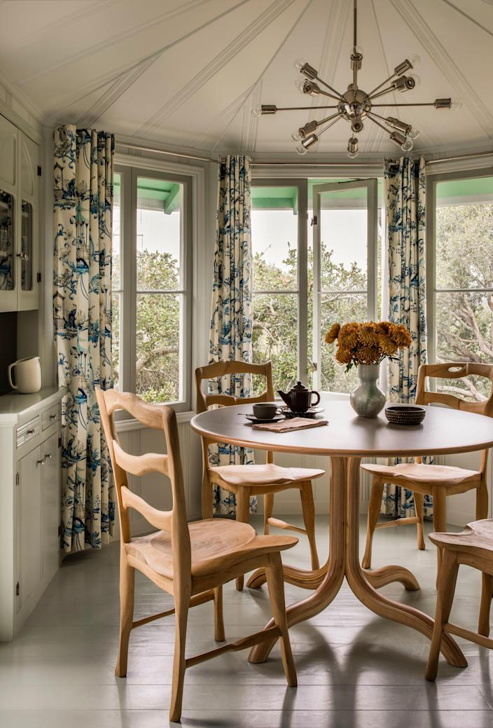 """""""They're traditional, but a little bit edgy,"""" says Carter of the hand-carved dining chairs by French furniture maker Paul Salet that surround a table by artist Matthew Day Jackson in the charming breakfast nook. The chandelier is by RH and the chinoiserie fabric for the curtains was sourced on Etsy."""