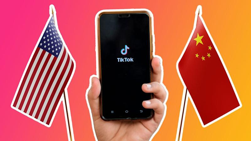 Between two flags - one US and one China - a hand holds up a phone with the TikTok logo on it