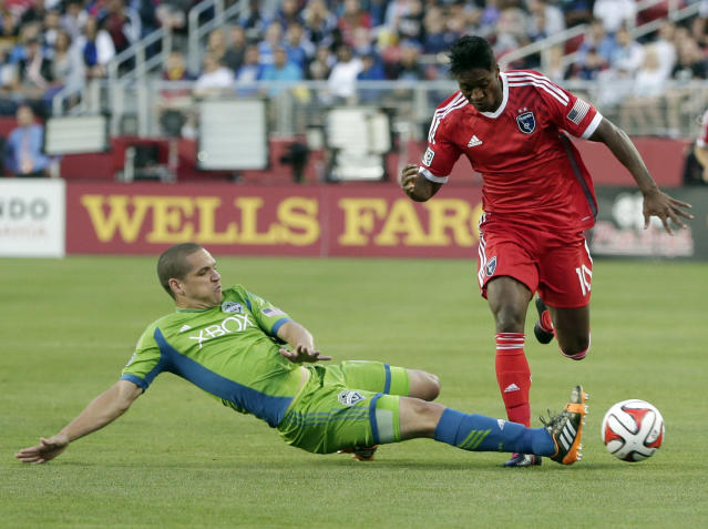 Seattle Sounders midfielder Osvaldo Alonso, left, makes a slide tackle next to San Jose Earthquakes midfielder Yannick Djalo during the first half of an MLS soccer match Saturday, Aug. 2, 2014, in Santa Clara, Calif. (AP Photo/Marcio Jose Sanchez)