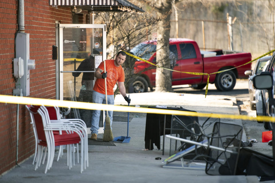 A man cleans up in front of Mac's Lounge, the scene of an early morning bar shooting, Sunday, Jan. 26, 2020, in Hartsville, S.C. (AP Photo/Sean Rayford)