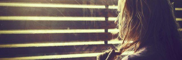 blonde woman looking through blinds into sunlight anxious upset