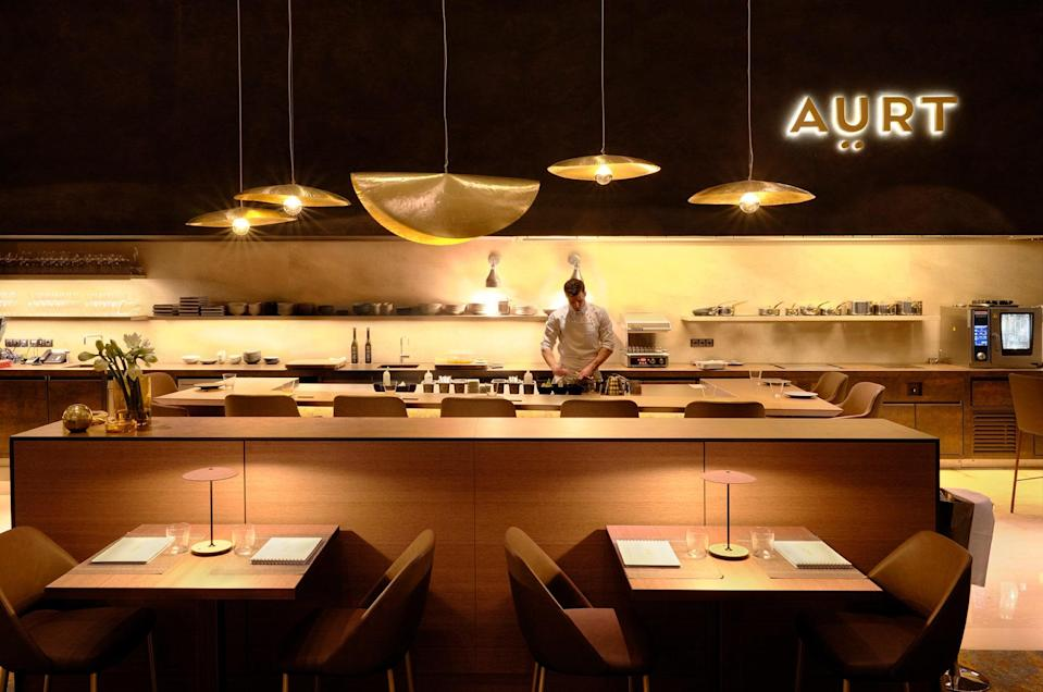 """<p><strong>So, can you tell us a little bit about this place?</strong> """"Welcome to lunch with the best chefs in Spain, and the best looking,"""" joked head chef Artur Martínez as we assumed our seats on a kitchen-facing pew. After earning a Michelin star for Capritx, in Terrassa, a small city 20 miles northwest of Barcelona, Martínez shut up shop, feeling he'd achieved all he could there. Aürt, his new tasting-menu-only restaurant in the lobby of the Hilton Diagonal Mar, has a clever setup where diners sit in front of the chefs and an arm's length from the hotplates. The feel is intimate and exclusive, and Martínez's sly humor adds to the warmth.</p> <p><strong>What is the crowd like?</strong> Laid-back foodies with laid-back afternoon schedules; after all, it takes a while to get through 15 courses. """"When Ferran Adrià comes—you know Ferran Adrià?"""" Martínez says, casually name-dropping the famed Michelin-starred chef, who loves this place.</p> <p><strong>What's the drink situation?</strong> A long, elegant, and accessible wine list comes courtesy of sommelier Eduard Tortajada, who is eager to guide your choice—whether it be a glass or several bottles.</p> <p><strong>How's the food?</strong> The seasonally changing menu is picture-perfect, with each course bidding for your love. On a recent visit, the red prawn salmorejo, a cold soup slightly denser than gazpacho, was a knockout, the prawn sweet and ripe with flavor. The cabbage with anchovies is good enough to change your opinion of cabbage forever.</p> <p><strong>Thoughts on the service?</strong> You're so close to the kitchen that the young team starts feeling more like colleagues than chefs. They're warm and chatty, and quick to step up for conversation if your lunch date nips to the loo.</p> <p><strong>What's the bottom line?</strong> Aürt is a good choice for a business lunch if a communal table isn't going to risk exposing corporate secrets. Otherwise, it's perfect for couples, catching up with a friend when bog-"""