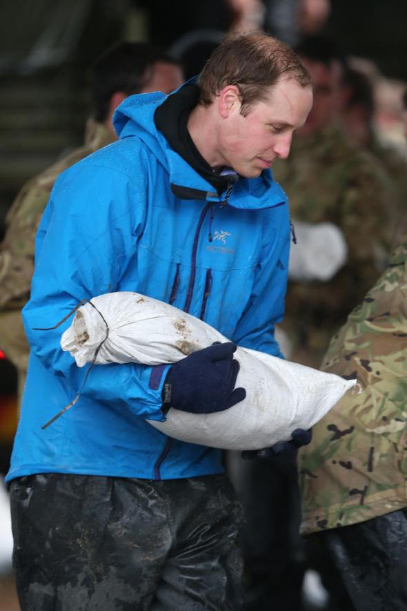 DATCHET, UNITED KINGDOM - FEBRUARY 14:  Prince William, Duke of Cambridge helps with flood defences around a petrol station in the centre of Dachet on February 14, 2014 in Datchet, United Kingdom.  (Photo by Peter Macdiarmid/Getty Images)