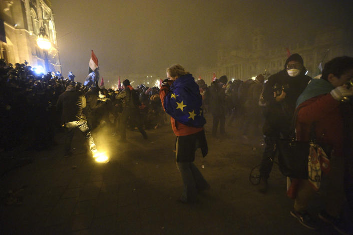 """Protesters demonstrate against the amendments to the labour code, dubbed """"slave law"""" by oppositional forces, at the parliament building in Budapest, Hungary, Thursday, Dec. 13, 2018. The rally, which was announced by the Free University and Students Trade Union student groups, started peacefully but police later responded to aggressive protestors with teargas. (Zoltan Balogh/MTI via AP)"""