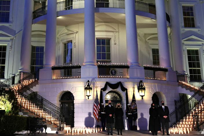 President Joe Biden, first lady Jill Biden, Vice President Kamala Harris and Harris's husband, Doug Emhoff, participate in a moment of silence at sundown Monday on the South Portico of the White House during a candlelight ceremony to mark the more than 500,000 lives lost in the U.S. to COVID-19. (Photo: Alex Wong/Getty Images)