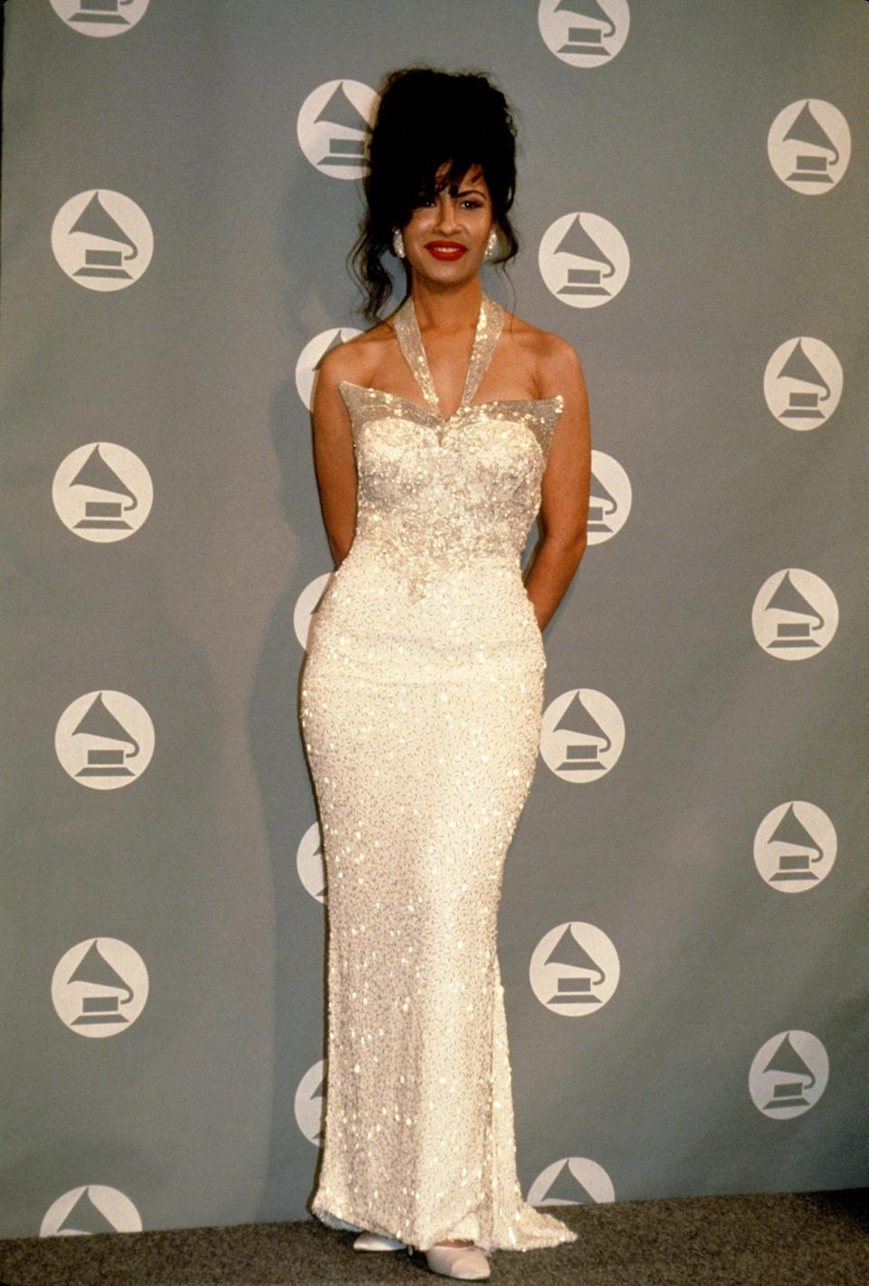 """<p>Just a year before her tragic death, Selena wore this dazzling crystal-covered white halter dress to the <a href=""""https://www.popsugar.com/latina/Did-Selena-Win-Grammy-43694425"""" class=""""link rapid-noclick-resp"""" rel=""""nofollow noopener"""" target=""""_blank"""" data-ylk=""""slk:1994 Grammys"""">1994 Grammys</a>, adding a pop of color with her signature red lips. </p>"""