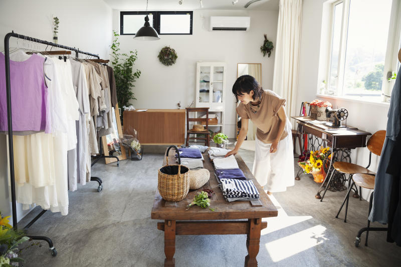 Japanese woman standing in a small fashion boutique, looking at T-Shirts on a coffee table.