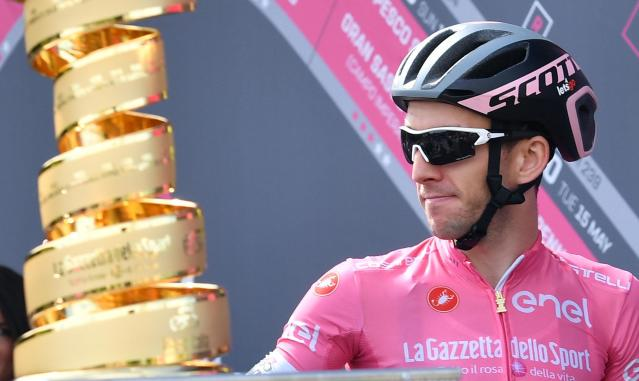 Britain's Simon Yates wears the pink jersey of the overall leader as he watches the trophy prior to the 10th stage of the Giro d'Italia cycling race, from Penne to Gualdo Tadino d'Italia, Italy, Tuesday, May 15, 2018. (Daniel Dal Zennaro/ANSA via AP)