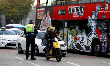 FILE PHOTO: A police traffic officer watches motorists entering the center on the first day of a city ordinance to ban certain vehicles without the proper sticker according to their emissions in Madrid, Spain, November 30, 2018.  REUTERS/Paul Hanna