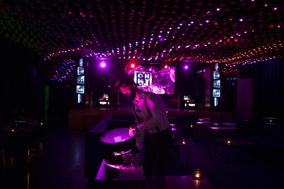 A waiter wearing a face mask to prevent the spread of coronavirus works in a discotheque in Madrid, Spain, early Saturday, July 25, 2020. Nightlife is becoming the new target of Spanish authorities attempting to contain a spike in coronavirus infections since the country ended a lockdown. The Catalonia regional government has shut nightlife venues in Barcelona, and on Friday officials in Madrid said they were considering a similar step. (AP Photo/Manu Fernandez)
