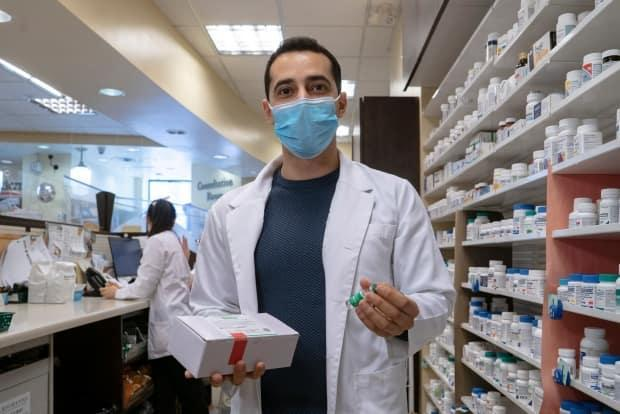 A pharmacist in Toronto holds up a box containing doses of the AstraZeneca-Oxford vaccine. Next week, the province will begin distributing some 55,000 doses that are set to expire May 31. (Sam Nar/CBC - image credit)