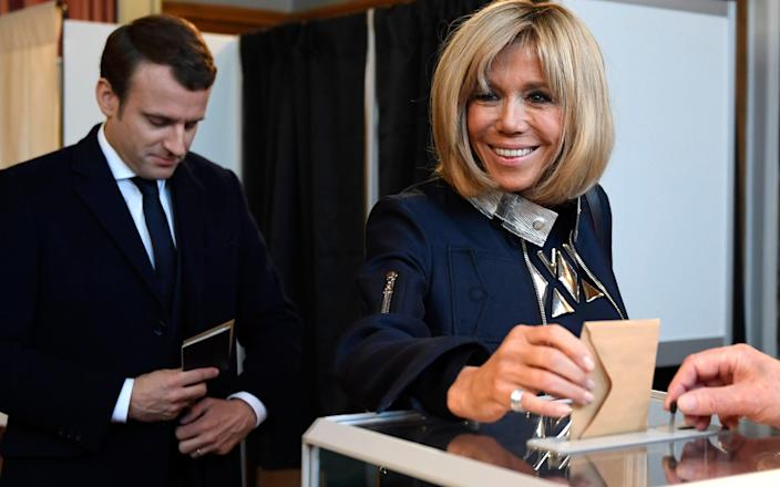 French presidential election candidate for the 'En Marche!' (Onwards!) political movement, Emmanuel Macron (L) looks on as his wife Brigitte Trogneux (R) casts her ballot at a polling station in Le Touquet, northern France - Credit: EPA