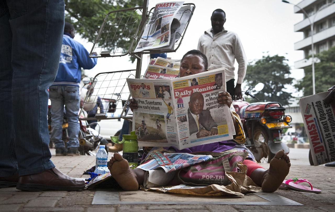 "A Ugandan newspaper seller reads a copy of the ""Daily Monitor"" newspaper on the street in Kampala, Uganda Tuesday, Feb. 25, 2014. The Ugandan ""Red Pepper"" tabloid newspaper published a list Tuesday of what it called the country's ""200 top"" homosexuals, outing some Ugandans who previously had not identified themselves as gay, one day after the president Yoweri Museveni enacted a harsh anti-gay law. (AP Photo/Rebecca Vassie)"
