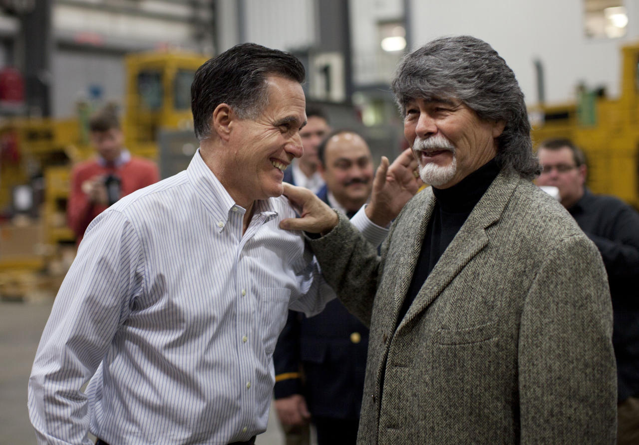 Republican presidential candidate, former Massachusetts Gov. Mitt Romney, left, laughs with the lead singer of the band Alabama, Randy Owen, during a campaign stop at Thompson Tractor on Friday, March 9, 2012, in Birmingham, Ala. (AP Photo/Evan Vucci)