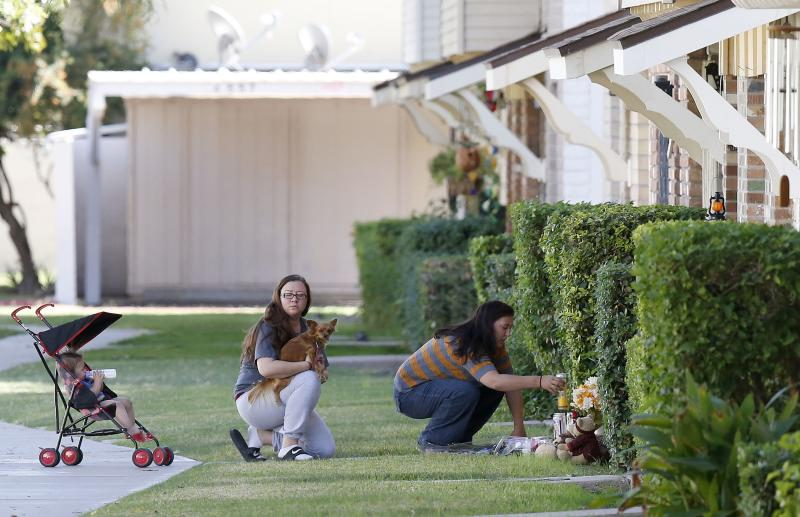 Neighbors add to a makeshift memorial set up at the Moore home on Monday Oct. 28, 2013, in Phoenix, to honor the four shooting victims. Police say loud barking dogs might have led to 56-year-old Michael Guzzo to kill four of his neighbors and the neighbors' two dogs before turning the gun on himself, and dying. The victims were identified as Bruce Moore, 66; his daughter, Renee Moore, 36; her husband, Michael Moore, 42, who took his wife's name; and Renee's son, Shannon Moore, 17. (AP Photo/Ross D. Franklin)