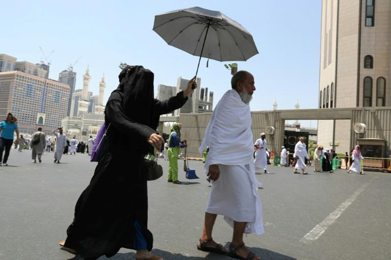 Muslims walk in Saudi Arabia's holy city of Mecca on August 18, 2018, ahead of the start of the annual hajj pilgrimage