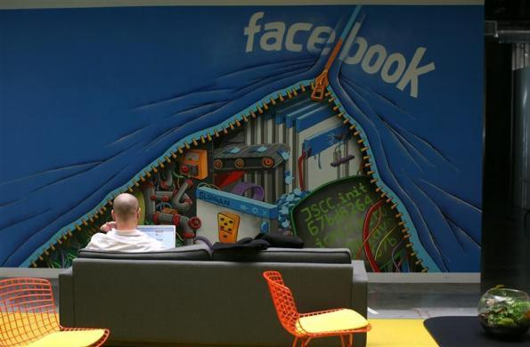 An employee works on a computer at the new headquarters of Facebook in Menlo Park, California January 11, 2012.