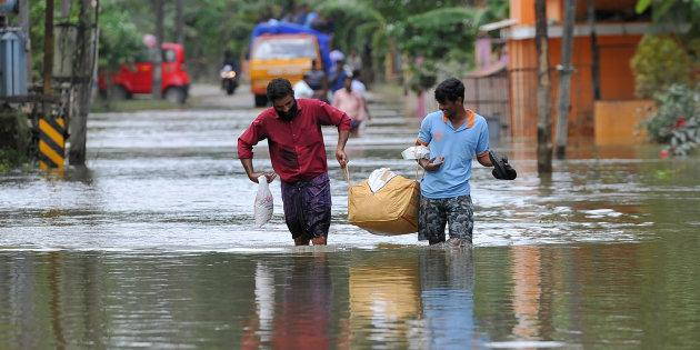 People carry food and water aid distributed to those stranded by floods in Pandanad in Alappuzha District in Kerala on August 21, 2018.