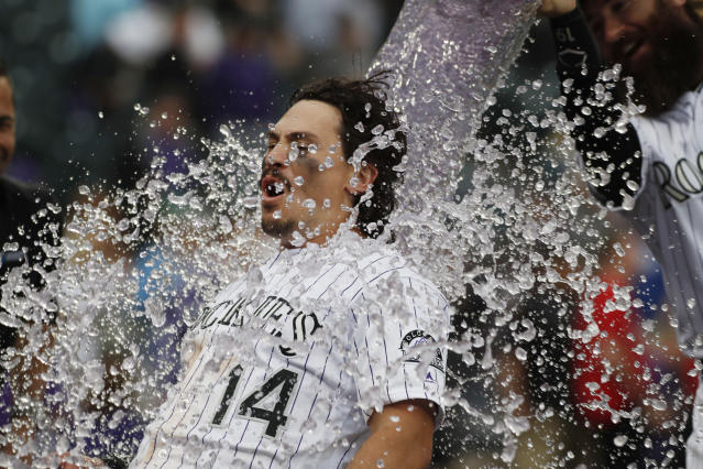 Colorado Rockies' Tony Wolters is doused by Charlie Blackmon after hitting a sacrifice fly to bring in the winning run off Baltimore Orioles relief pitcher Mychal Givens in the ninth inning of a baseball game, Sunday, May 26, 2019, in Denver. (AP Photo/David Zalubowski)